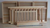 Alle Teile unseres 10er-Holzregals. 10 Schubladen, 2 Seitenteile, 4 Querstreben ein Deckelgitter sowie 4 Gewindestangen mit 8 Muttern zum Befestigen. Beim 15er sind es 5 weitere Schubladen und längere Seitenteile.